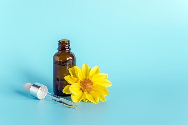 Olejek eteryczny w otwartej brązowej kroplomierzu z leżącą szklaną pipetą i żółtym kwiatem na błękitnym tle