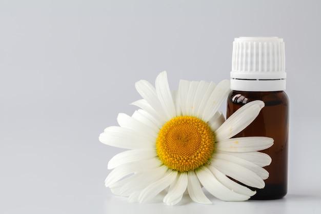 Olejek eteryczny w szklanej butelce ze świeżymi kwiatami rumianku, zabiegi kosmetyczne. koncepcja spa
