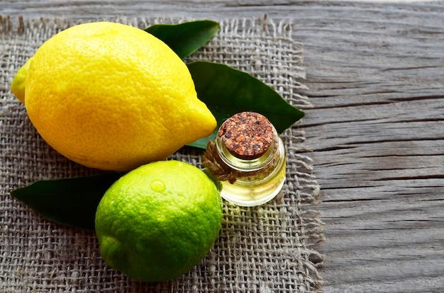 Olejek eteryczny z cytryny w szklanej butelce ze świeżymi owocami cytryny i limonki. olejek cytrynowy do spa, aromaterapii i pielęgnacji ciała. wyciąg olej z cytryny. selektywne ustawianie ostrości.