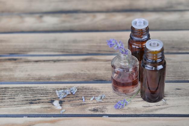 Olejek eteryczny z lawendy w butelce i kwiatach na drewnianym stole