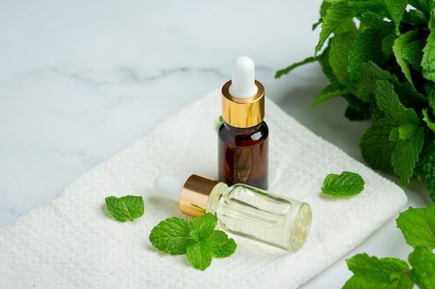 Olejek eteryczny z mięty pieprzowej w butelce ze świeżą zieloną miętą