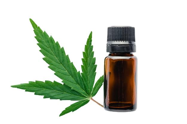 Olejek eteryczny z oleju konopnego w czarnej szklanej butelce z liśćmi konopi na białym tle. liść konopi z produktem kosmetycznym do pielęgnacji skóry.