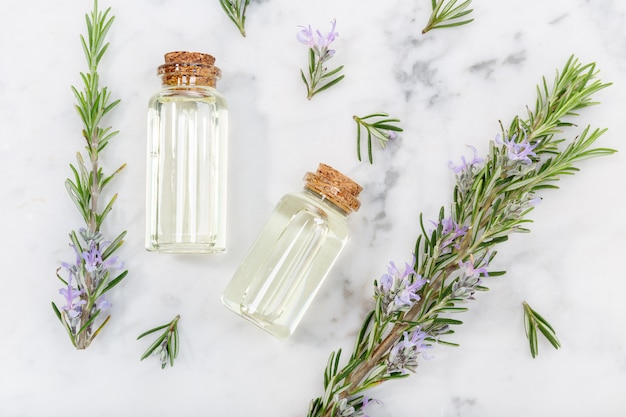 Olejek eteryczny z rozmarynu w szklanej butelce i gałązkach na marmurowym stole. olejek szałwiowy rosmarinus. widok z góry