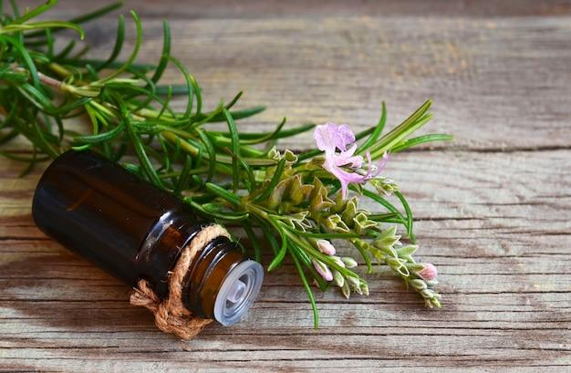Olejek eteryczny z rozmarynu w szklanej butelce z kroplomierzem ze świeżym zielonym ziołowym rozmarynem na starym drewnie
