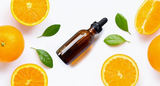 Olejek eteryczny ze świeżych pomarańczowych owoców cytrusowych z liśćmi na białym