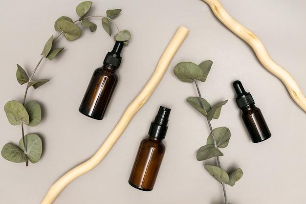 Olejek eukaliptusowy w ciemnej szklanej butelce z zakraplaczem z ekstraktem ziołowym, koncepcja pielęgnacji skóry i medycyny alternatywnej, liście eukaliptusa na tle.