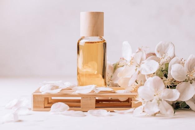 Olejek kosmetyczny, aromatyczny lub do masażu na drewnianym podium w formie palety, na jasnej powierzchni gipsowej z kwiatami jabłoni