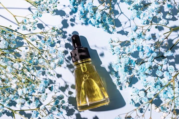 Olejek kosmetyczny z naturalnymi składnikami na niebieskim tle z kwiatami. koncepcja leczenia pielęgnacji skóry. niemarkowy pakiet do projektowania