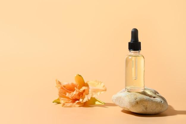 Olejek lub esencja kosmetyczna w szklanej butelce na kamiennym podium zdobiła świeże kwiaty lilii na beżowej przestrzeni