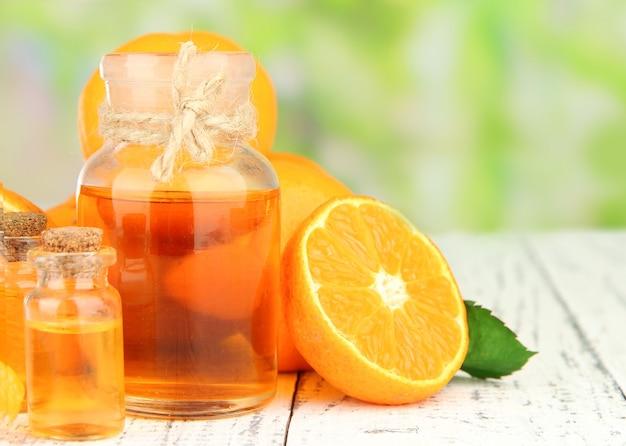 Olejek mandarynkowy i mandarynki na drewnianym stole na niewyraźną naturę