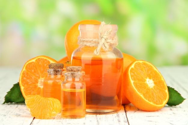 Olejek mandarynkowy i mandarynki na drewnianym stole, w przestrzeni natury