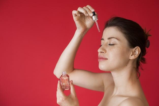 Olejek przeciwstarzeniowy nakładany na twarz kaukaskiej kobiety z piegami na czerwonej ścianie