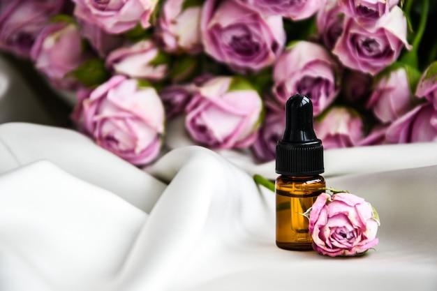 Olejek różany. spa i aromaterapia kwiat róży butelka olejku z pipetą na satynowej tkaninie w kolorze szampana. butelki olejku różanego i świeżych kwiatów. skopiuj miejsce