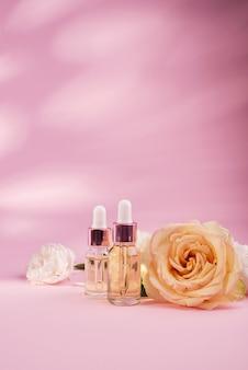 Olejek różany w butelce kosmetycznej w pobliżu świeżych kwiatów róży na różowym tle. ekstrakt z kwiatów róży.