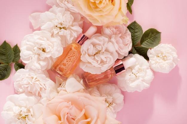 Olejek różany w butelce kosmetycznej w pobliżu świeżych kwiatów róży na różowym tle. kosmetyki z widokiem z góry na płasko