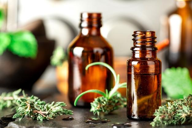 Olejki eteryczne w butelce z brązowego szkła, tymianku, rozmarynu i mięty na stole. ziołowy olejek eteryczny, aromaterapia. kategoria styl życia