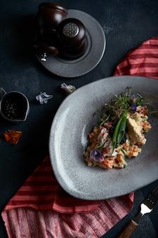Olivier z mięsem kraba w pięknej misce w ostrygach, w ciemności. jedzenie w żaden sposób, moda na jedzenie. zdrowe odżywianie.
