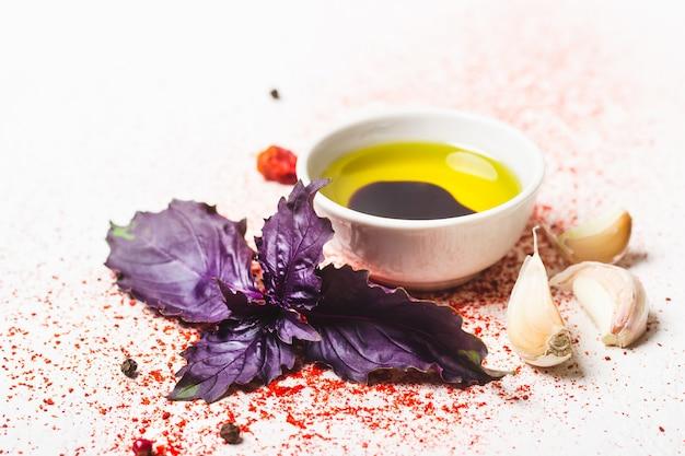 Oliwa z oliwek, bazylia i przyprawy na białym tle zbliżenie.