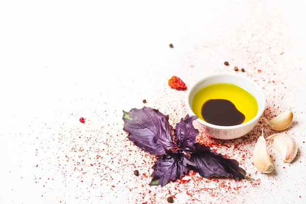 Oliwa z oliwek, bazylia i przyprawy na białym tle.