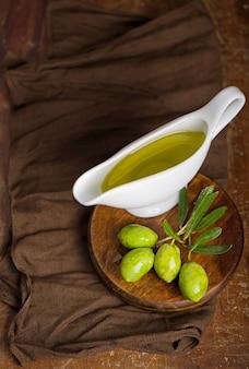 Oliwa z oliwek i gałązka oliwna na czarnym tle.