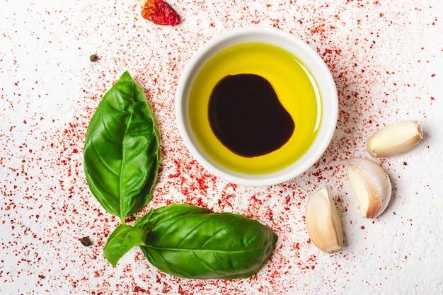 Oliwa z oliwek i przyprawy na białym tle zbliżenie.