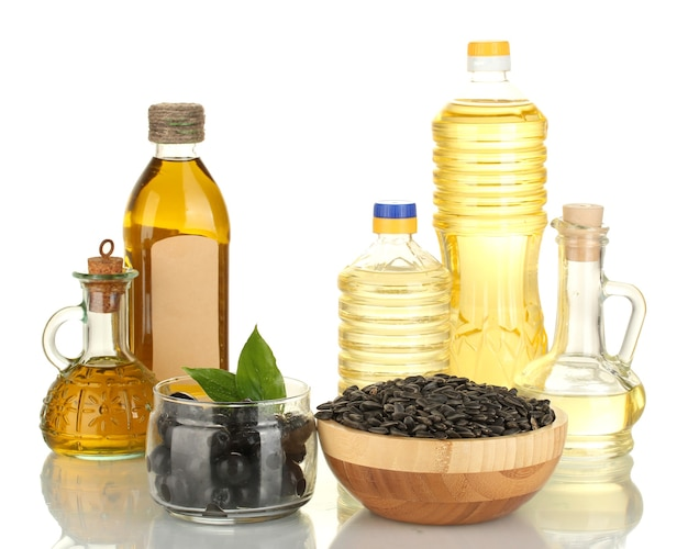 Oliwa z oliwek i słonecznik w butelkach i małe karafki na białym tle