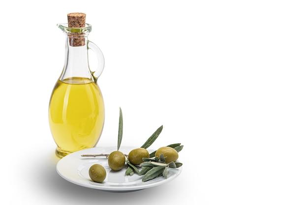 Oliwa z oliwek w szklanej butelce i oliwki w białym talerzu ceramicznym. biała ściana.