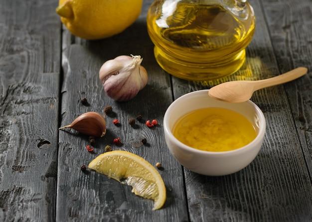 Oliwa z oliwek z czosnkiem i cytryną w białej misce na ciemnym czarnym stole. sos do sałatki dietetycznej.