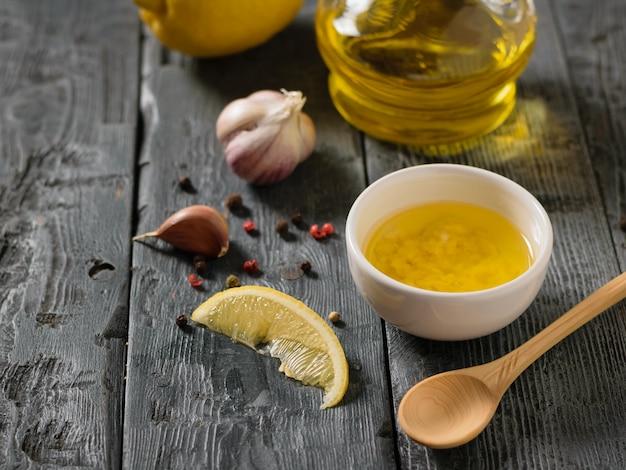 Oliwa z oliwek z czosnkiem i cytryną w białej misce na drewnianym stole. sos do sałatki dietetycznej.