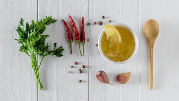 Oliwa z oliwek z czosnkiem, pieprzem, cytryną i natką pietruszki w białej misce na białym stole. sos do sałatki dietetycznej. widok z góry.