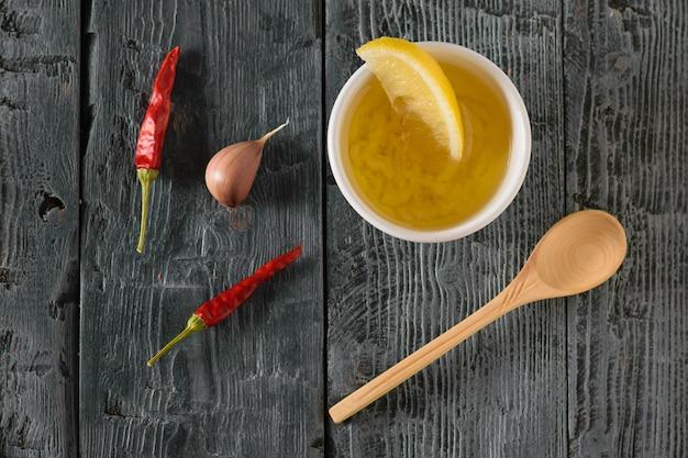 Oliwa z oliwek z czosnkiem, pieprzem i cytryną w białej misce na drewnianym stole. sos do sałatki dietetycznej. widok z góry.