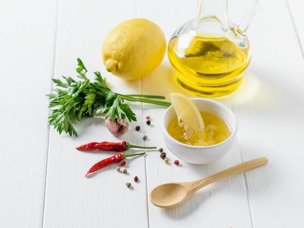 Oliwa z oliwek z czosnkiem, pieprzem, natką pietruszki i cytryną w białej misce na stole. sos do sałatki dietetycznej.