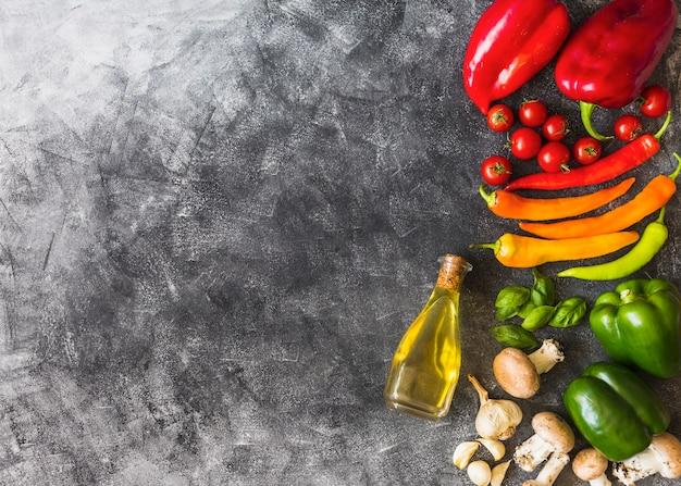 Oliwa z oliwek z kolorowymi warzywami na grunge textured tle