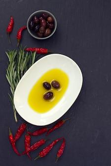 Oliwa z oliwek z oliwkami, chili i rozmarynem na czarnej powierzchni