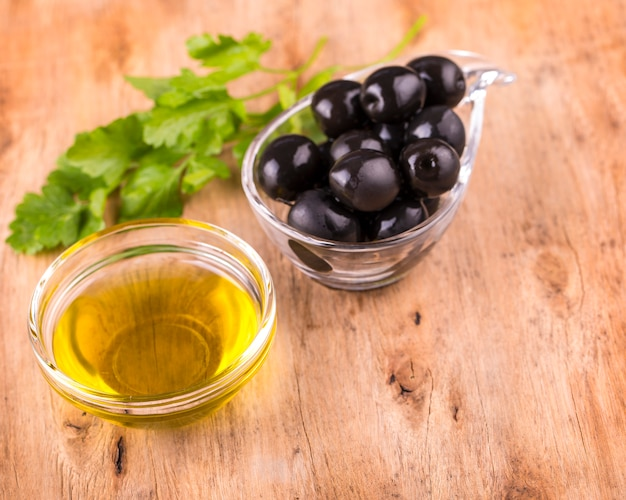 Oliwki i zdrowy kubek oliwy z oliwek z natką pietruszki na starym drewnianym stole