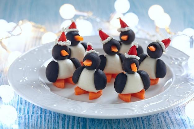 Oliwkowa przekąska pingwinów z mozzarellą, marchewką i papryką w czapce mikołaja