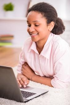 Oliwkowa uczennica kłaść na dywanie i używa laptop.