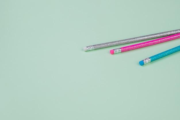 Ołówek i gumki na białym tle na pastelowym tle. kosmos. piśmiennictwo, pisanie towarów. szkolny instrument, elementy do projektowania, koncepcja edukacji, kolory trandy.