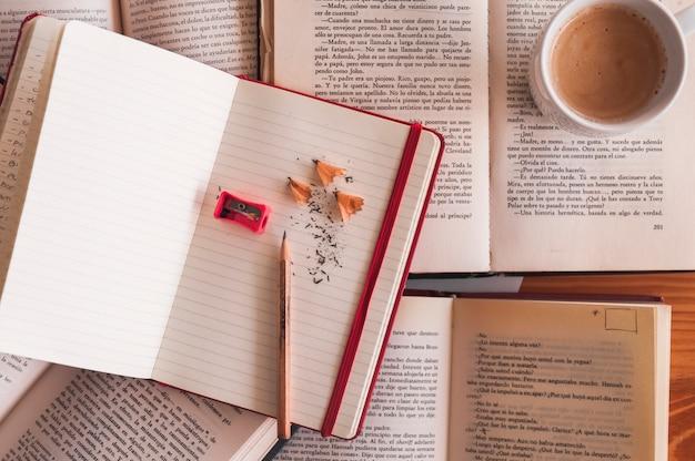 Ołówek i notatnik blisko kawy i książek
