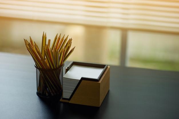 Ołówek i uwaga umieszczony na biurku wykonawczym. umieszczony przy oknie