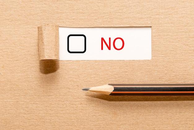 Ołówek na podartym papierze z tekstem nie i polem wyboru. pojęcie podejmowania decyzji