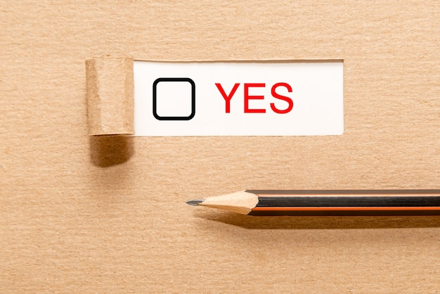 Ołówek na podartym papierze z tekstem tak i polem wyboru. pojęcie podejmowania decyzji