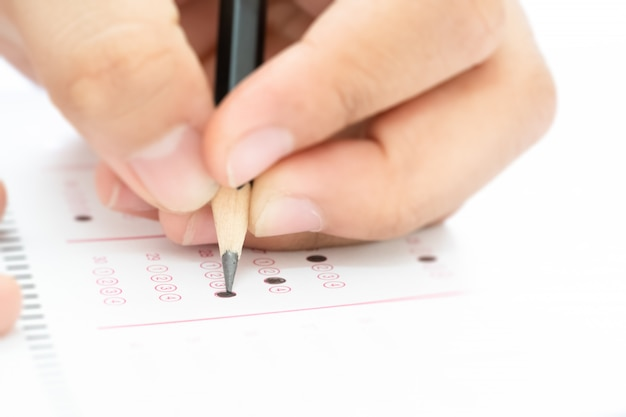 Ołówek na ręce uczeń pisze odpowiedź na egzamin testowy