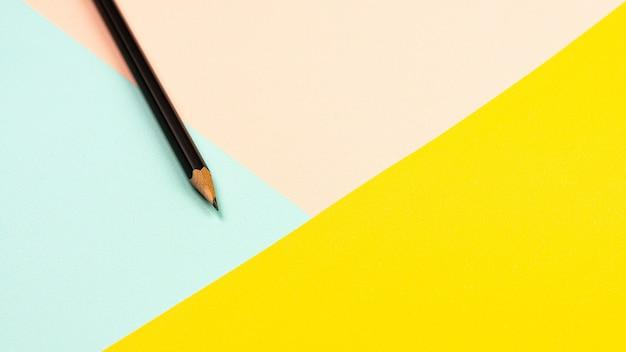 Ołówek na różowym, niebieskim i żółtym tle papieru.