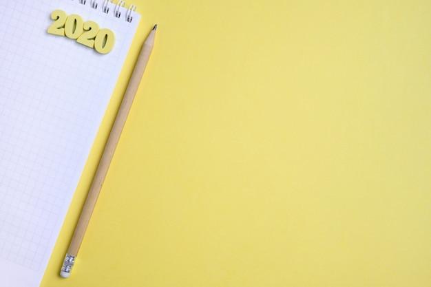 Ołówek obok notatnika i drewniane figury 2020 na żółtym tle.