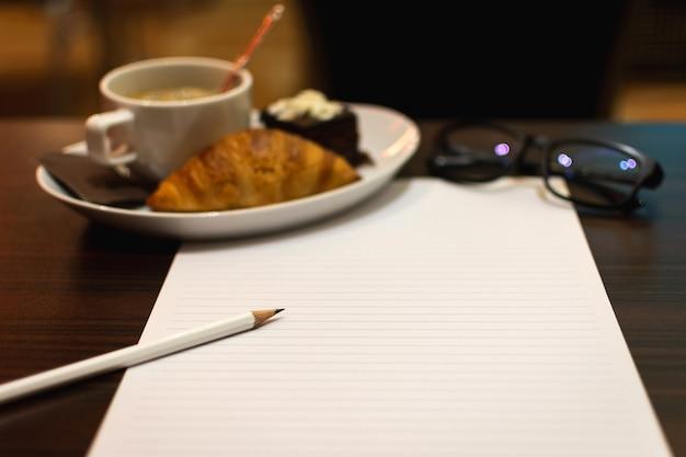 Ołówek położył na białym papierze z kawą i śniadaniem chlebowym.