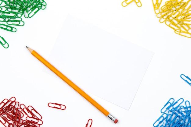 Ołówek, spinacze do papieru leżą pod różnymi kątami arkusza na białym tle. obraz bohatera i miejsce na kopię.