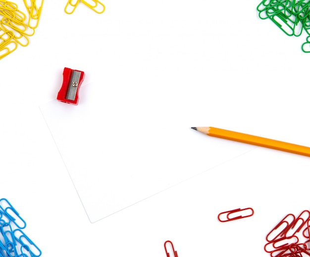 Ołówek, temperówka, spinacze do papieru leżą pod różnymi kątami arkusza na białym tle. obraz bohatera i miejsce na kopię.