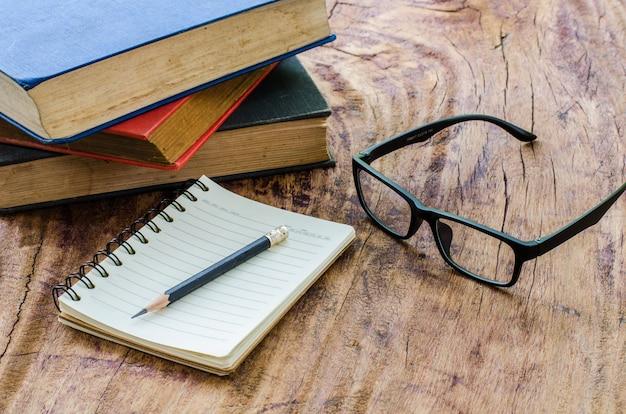 Ołówek umieszczony na stosie książek i notebooków z okularów na drewnianej podłodze.