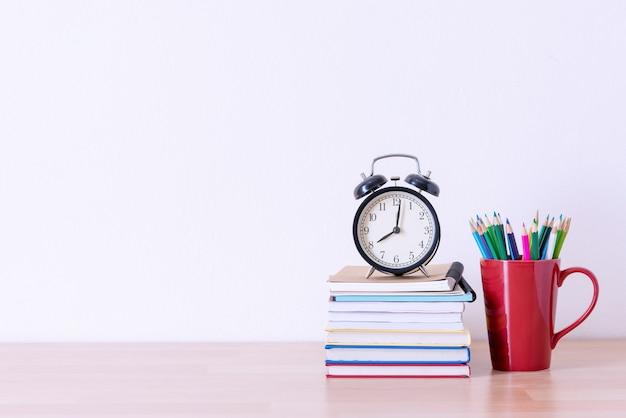 Ołówek w czerwony kubek i zegar alram na książki stos na drewnianym stole